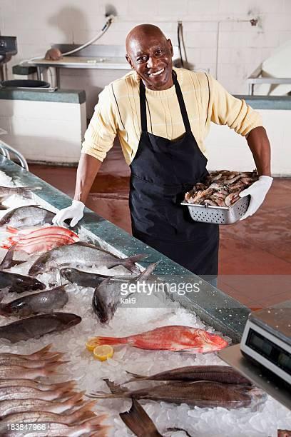 Trabajador en el mercado de pescados y mariscos frescos de display