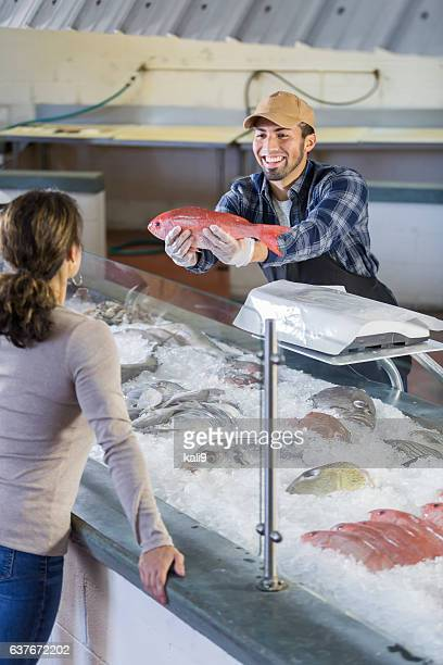 Worker in seafood market helping customer
