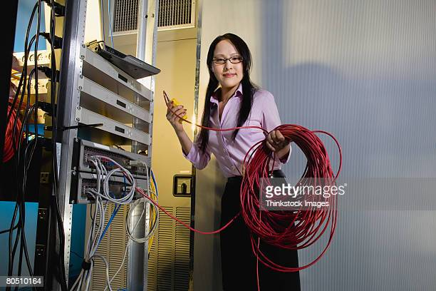 Worker in server room testing network cable