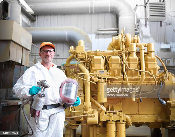 Worker in spray booth with engine
