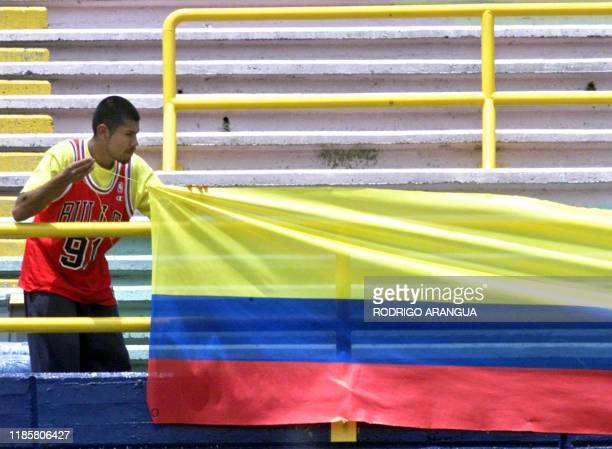 A worker in the Atanasio Girardot Stadium in Medellin Colombia hangs a Colombian flag 10 July 2001 The rescheduled Copa America tournament begins 11...