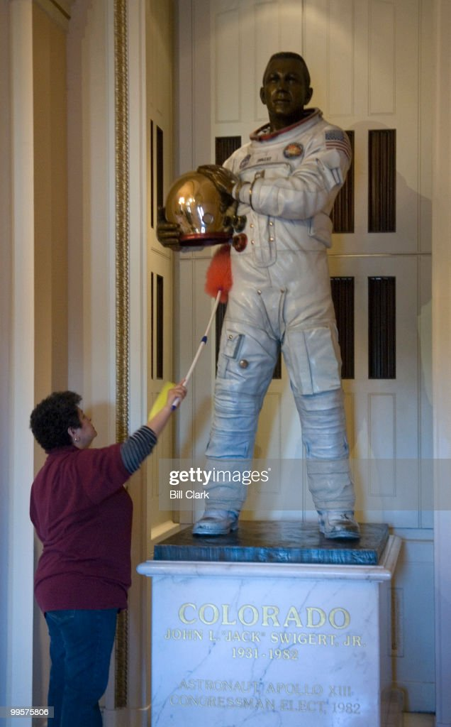 A worker in the Capitol, who refused to be identified, dusts the statue of Apollo 13 astronaut Jack Swigert on the first floor of the Capitol on the House side, Monday, Jan. 29, 2007.