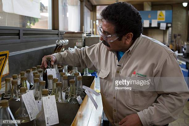 A worker in the chemisty department reaches for a bottle crude oil to be tested at the Petroleos Mexicanos Miguel Hidalgo Refinery in Tula de Allende...