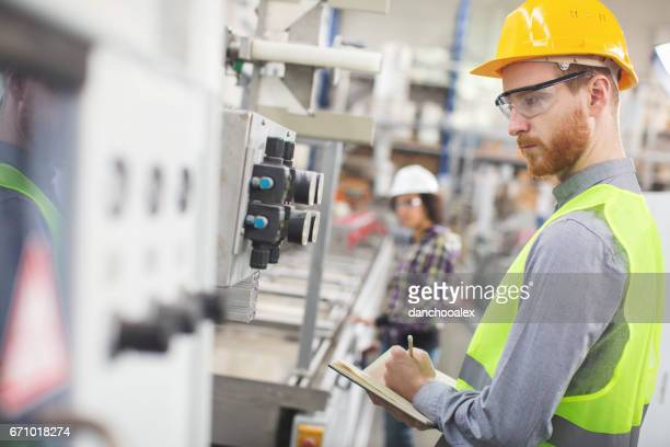Worker in the factory taking readings