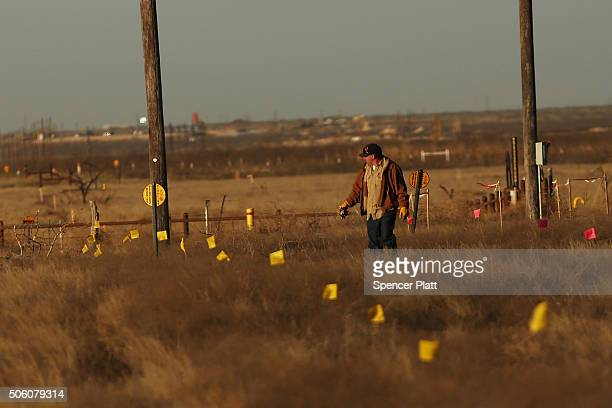 A worker in the oil industry walks through an area where a new pipeline is being laid in the Permian Basin oil field on January 21 2016 in the oil...