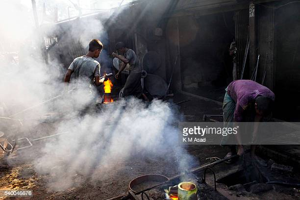 SADARGHAT DHAKA BANGLADESH A worker in the smoke at a ship propeller making factory in sadarghat dockyard Dhaka Bangladesh June 02 2016 The laborers...