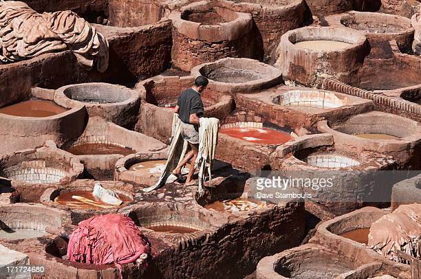 CONTENT] worker in the thousand year old leather tannery in Fes Morocco