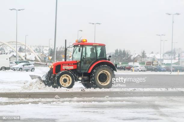 Worker in the Zetor 7341 tractor snowclearing parking lot in front of the shopping center is seen in Gdansk Poland on 19 January 2018 Heavy snow fall...