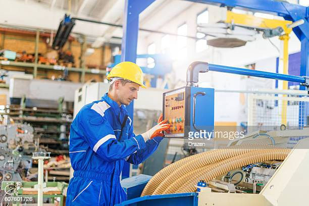 Worker in uniform starting the production process on machine