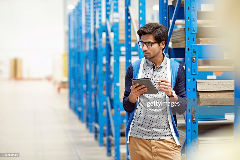 Worker in warehouse checking stocks : Stock Photo