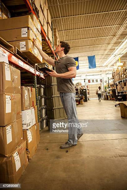 worker in warehouse selecting items from cardboard boxes - heshphoto stock pictures, royalty-free photos & images