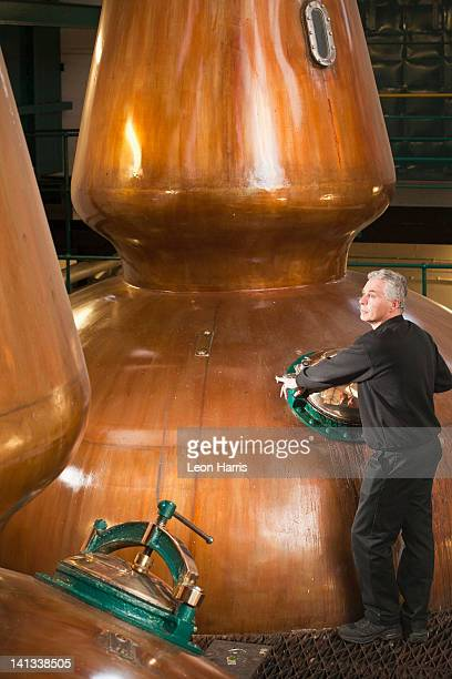 worker in whisky distillery - distillery stock pictures, royalty-free photos & images