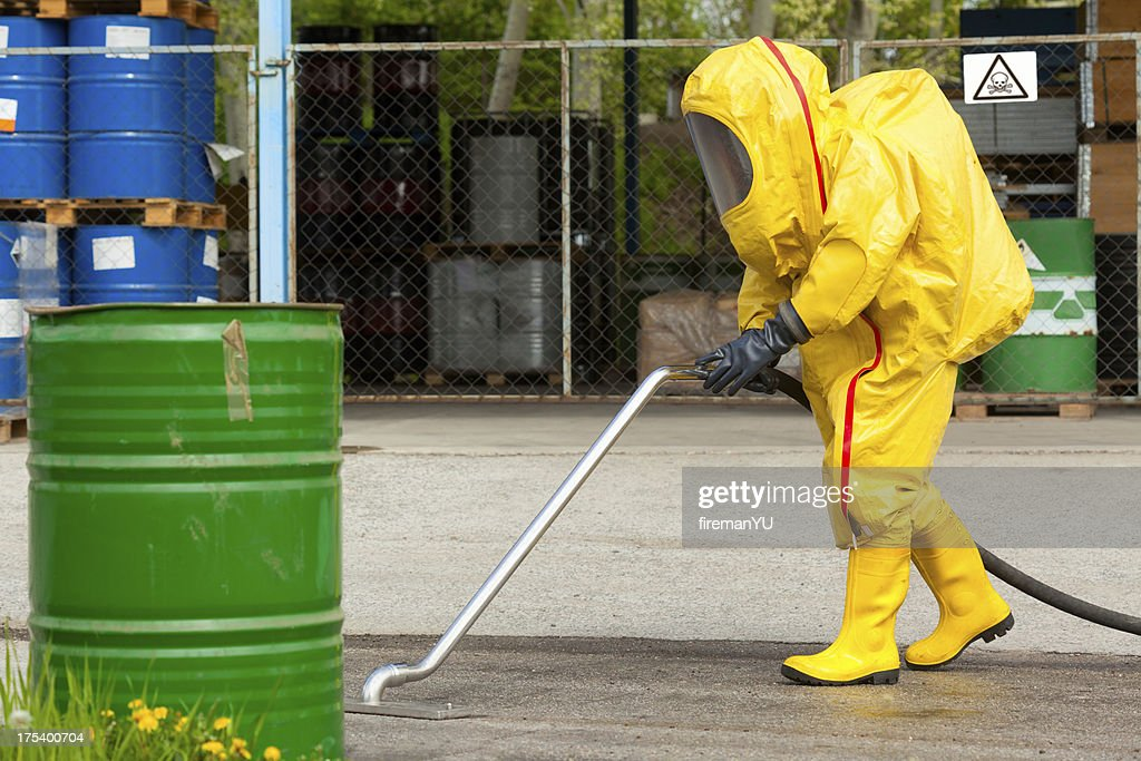 Worker in yellow hazmat suit cleaning ground : Stock Photo