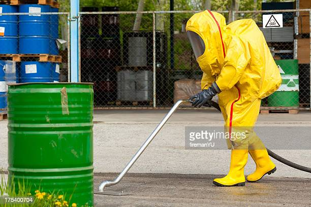 Worker in yellow hazmat suit cleaning ground