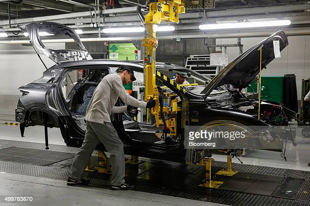 A worker inserts a dashboard into an Infiniti Q30 automobile on the production line at the Nissan Motor Co production plant in Sunderland UK on...