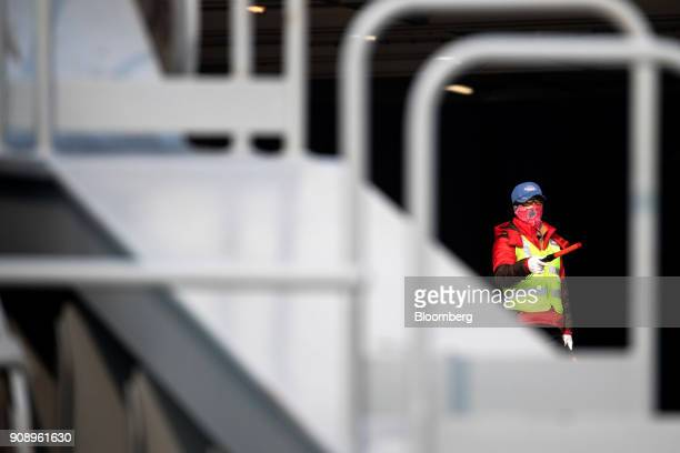A worker inside the Hyundai Glovis Co rollon/rolloff vehicles carrier cargo ship directs the drivers of Kia Motors Corp vehicles bound for export at...