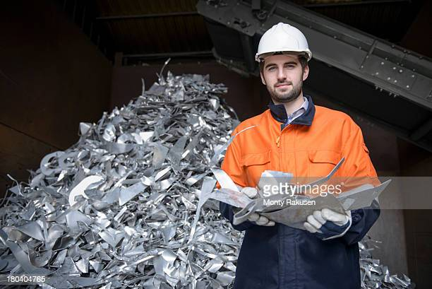 Worker inspecting aluminium scrap in aluminium recycling plant, portrait