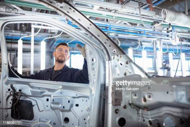 worker inspecting car body in car factory - working stock pictures, royalty-free photos & images
