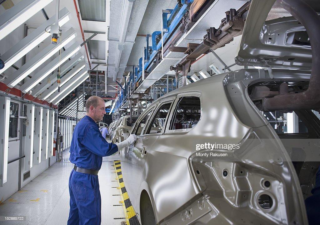 Worker inspecting car body in car factory : Foto de stock