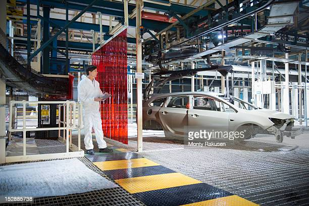Worker inspecting car body in car factory