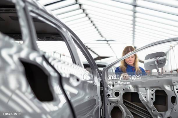 worker inspecting car body in paint inspection area in car factory - chassis stock pictures, royalty-free photos & images