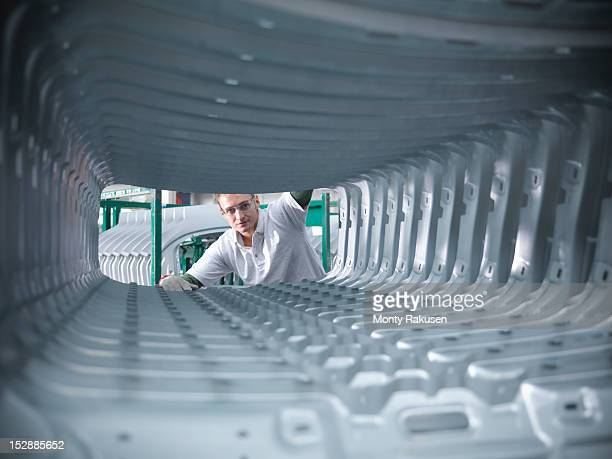 worker inspecting car body pressings in car factory - human body part ストックフォトと画像