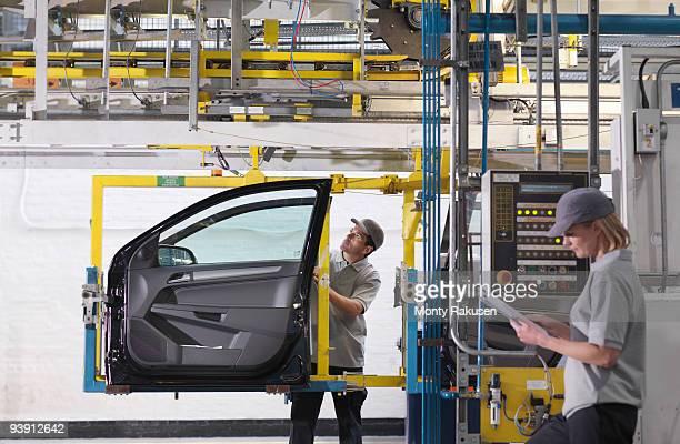 Worker Inspecting Car Door In Plant