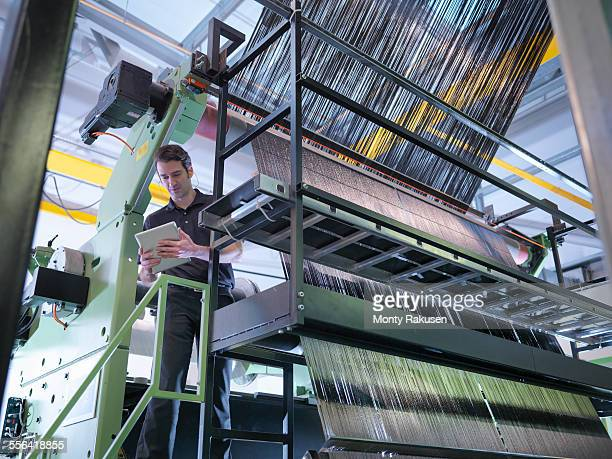 Worker inspecting carbon fibre on loom in carbon fibre factory