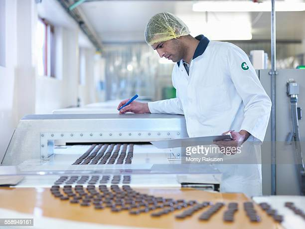 worker inspecting chocolate on production line in chocolate factory - chocolate factory stock photos and pictures