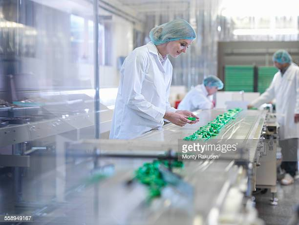 worker inspecting chocolate on production line in chocolate factory - candy factory stock pictures, royalty-free photos & images