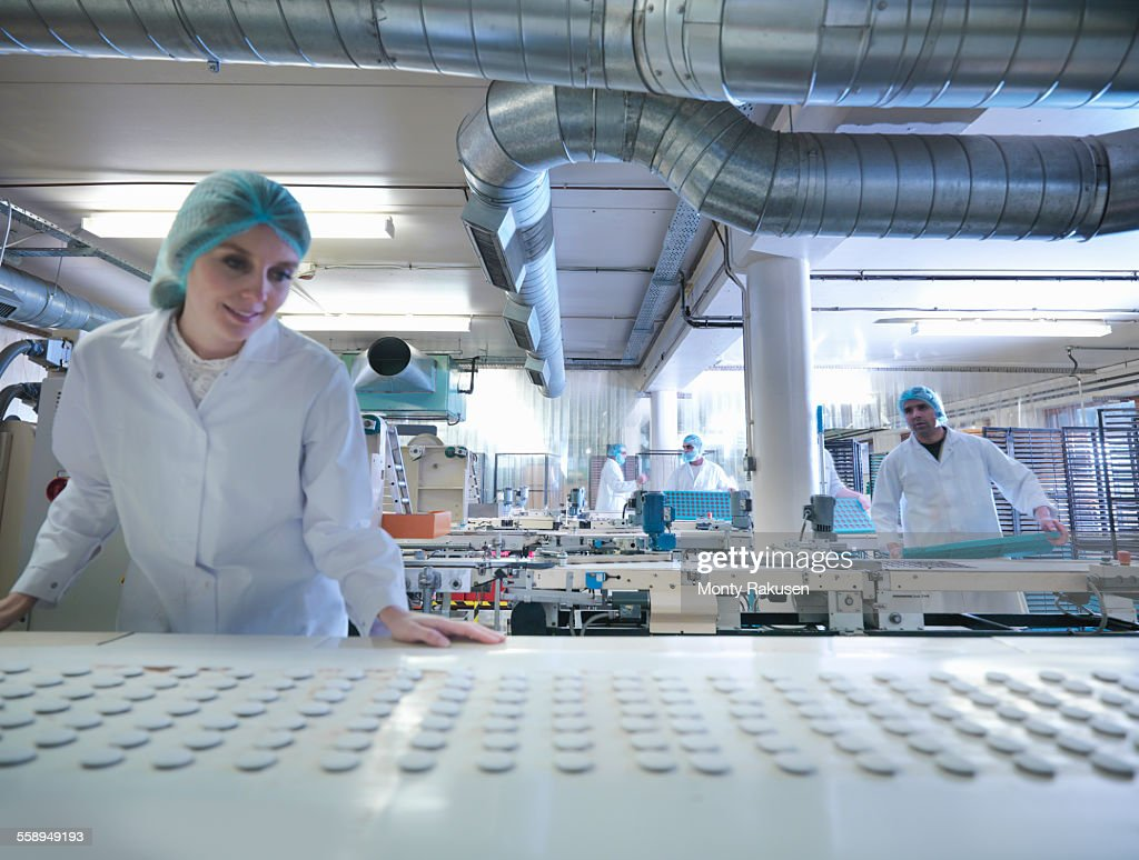 Worker inspecting chocolates on production line in chocolate factory : Stock Photo