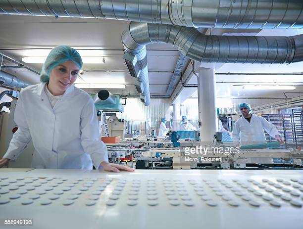 worker inspecting chocolates on production line in chocolate factory - chocolate factory stock photos and pictures