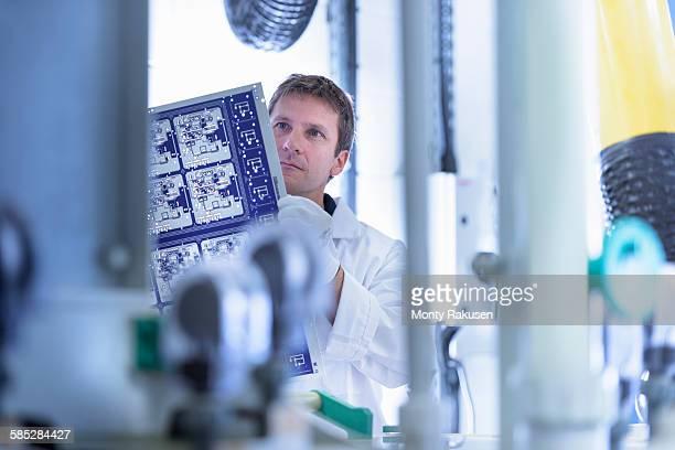 worker inspecting circuit board by processing plant in circuit board factory - monty rakusen stock-fotos und bilder