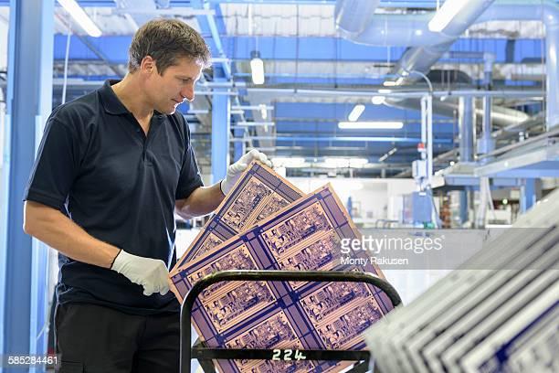 worker inspecting circuit board in circuit board factory - monty rakusen stock-fotos und bilder