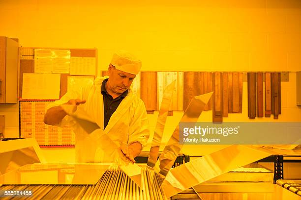 worker inspecting circuit board under photographically safe light in circuit board factory - monty rakusen stock pictures, royalty-free photos & images