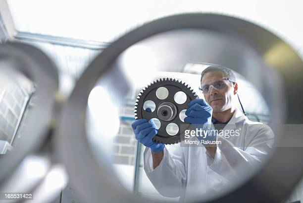 Worker inspecting engineering products that are being cleaned using ultrasonics, view through equipment