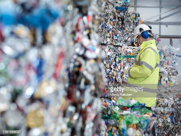 worker inspecting mixed waste in waste recycling plant. - tin can stock pictures, royalty-free photos & images