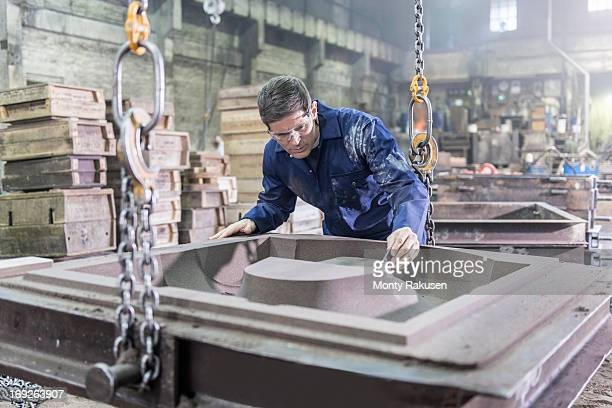 Worker inspecting mould in foundry