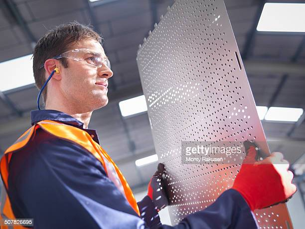Worker inspecting newly cut parts in sheet metal factory