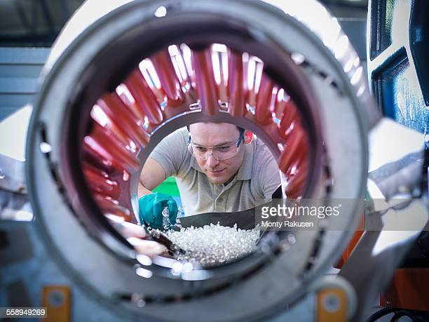 Worker inspecting parts from plastic injection moulding machine in plastics factory