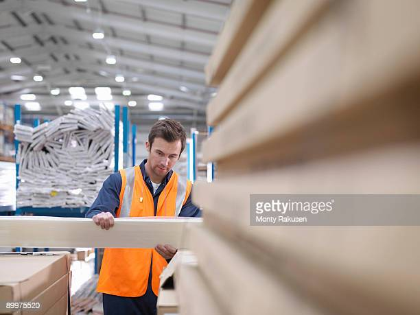 worker inspecting product in warehouse - monty rakusen stock pictures, royalty-free photos & images