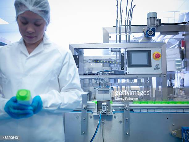 Worker inspecting products on production line in pharmaceutical factory