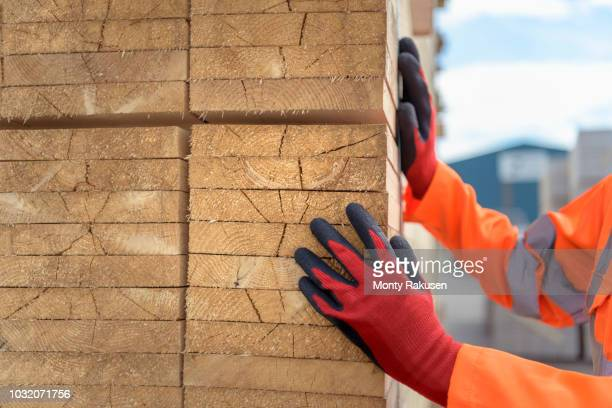 worker inspecting stacks of timber in storage at port - construction material stock pictures, royalty-free photos & images
