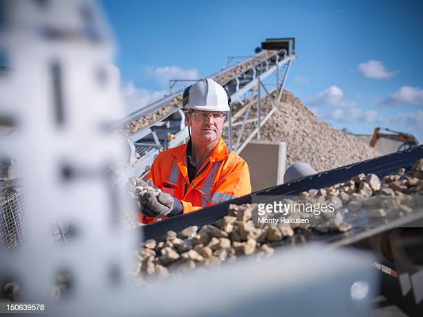 Worker inspecting stone screening and crushing machine in quarry