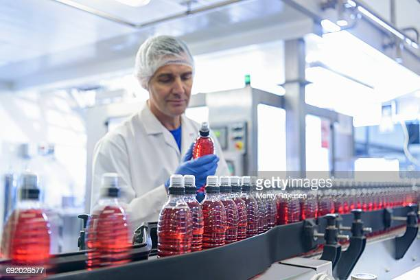 Worker inspecting water bottle on production line in spring water factory