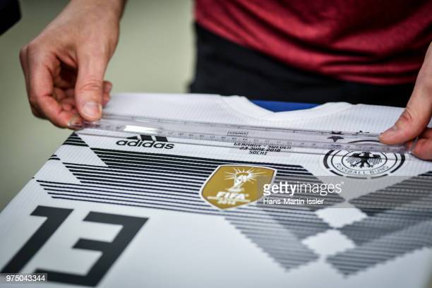 A worker inspects a customized home jersey of Thomas Mueller for the world cup match of Germany against Sweden during a visit of the Adidas...