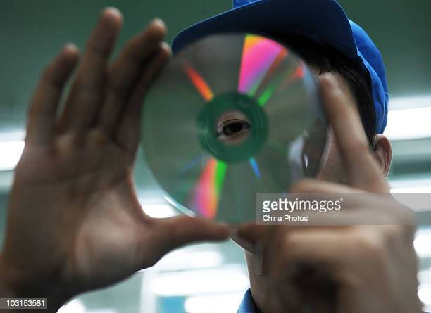 Worker inspects a digital optical disc on a production line of the Yingshan Digital Technology Culture Development Company on July 29, 2010 in...