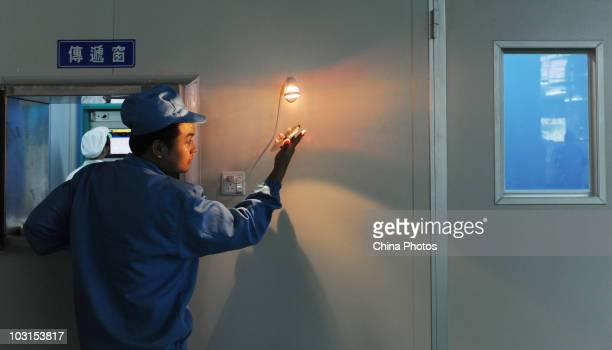 Worker inspects a disc in a master disc plant of the Yingshan Digital Technology Culture Development Company on July 29, 2010 in Shifang of Sichuan...