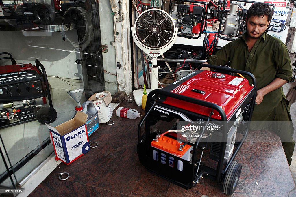 A worker inspects a Grannitto-branded generator at a generator wholesaler in Karachi, Pakistan, on Monday, May 13, 2013. Nawaz Sharif was headed for a record third term as prime minister of Pakistan as unofficial results from a landmark election gave him the convincing win he sought to tackle a slumping economy and growing militancy. Photographer: Asim Hafeez/Bloomberg via Getty Images