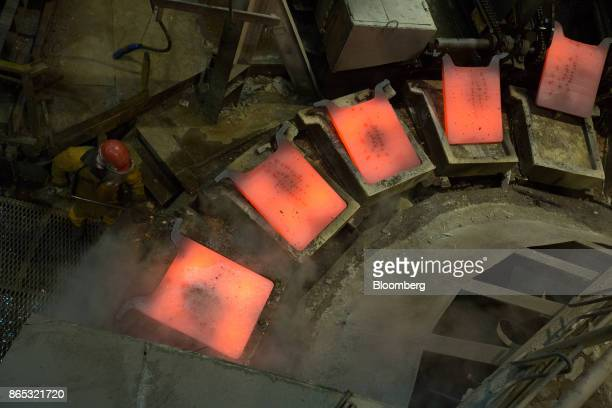A worker inspects a newlycast copper anode sheet as it cools in its mold at the MMC Norilsk Nickel PJSC copper refinery in Norilsk Russia on Thursday...